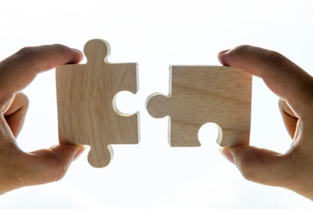 Macro shot of jigsaw puzzles teamwork concept